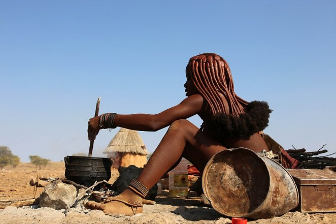 A woman wearing traditional Himba tribal clothes prepares food outside her home