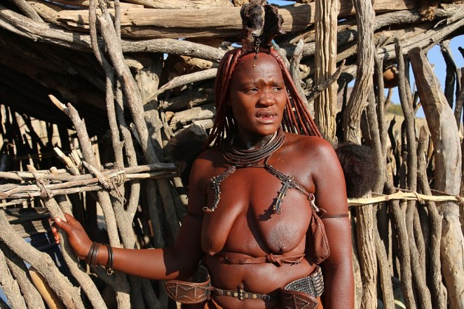 A woman stands in front of a fence in the breathtaking rural setting in Namibia which is home to the Himba tribe