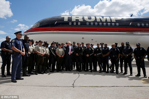 Above Trump poses for a photo with police officers who formed part of his motorcade on the tarmac in Detroit