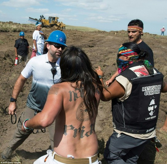 Security agents (left in blue helmet) confront protesters on the worksite for the Dakota Access Pipeline (DAPL) oil pipeline, near Cannonball, North Dakota, on Saturday