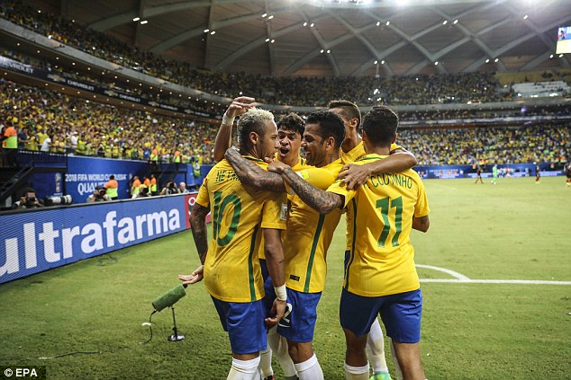 Neymar is mobbed by his Brazilian team-mates after coming up with the winner