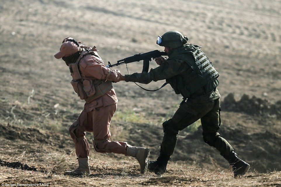A soldier pretends to take an enemy hostage during the war game, with both men wearing different colour uniforms to differentiate between the two sides