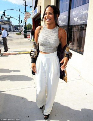 Peak: Christina Milian showed just a bit of her taut tummy in a grey knit crop top and flowy white trousers