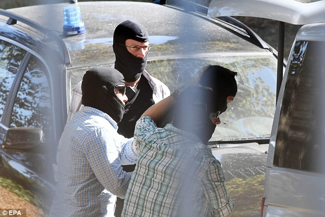 The terror suspects (piutured being led to van in centre) arrested in an asylum seekers home in Schleswig-Holstein arrived in Europe with fake passports crafted for them by ISIS forgers and accompanied by two of the Paris attackers