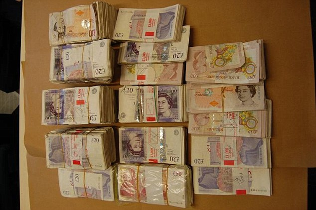 Images released by police shows a huge pile of cash uncovered during the investigation