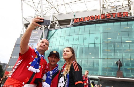Manchester United supporters take selfies outside Old Trafford in the build-up to kick-off on Saturday lunchtime