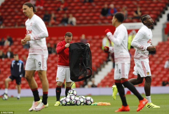 United captain Wayne Rooney empties a bag of balls having been dropped to the bench by manager Jose Mourinho