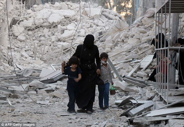 A Syrian mother leaves the area with her two young children following the airstrike