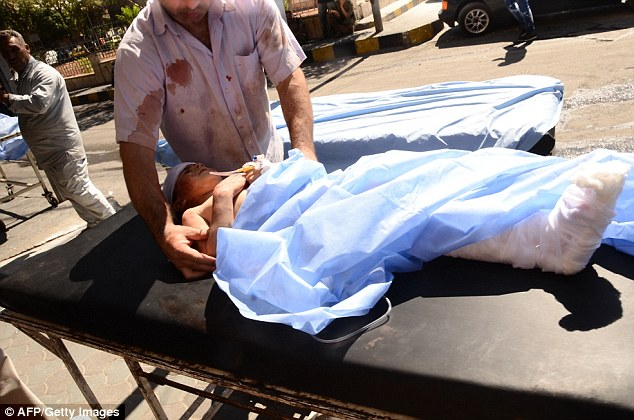 A wounded Syrian child is rushed into a hospital after she was hit by mortar shells that targeted Aleppo's government controlled Aziziyah and Suleimaniyah neighbourhoods on Thursday