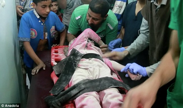Injured Sabah Sheikh Qasim is a six-year-old Syrian twin. She is being taken to hospital after she was pulled out from the wreckage of a five-storey building hit by Assad regime forces' air strikes in Shaar town of Aleppo on Thursday