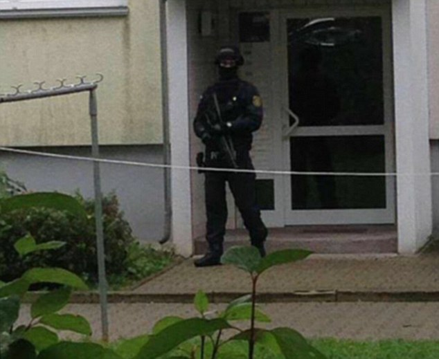 Residents have been ordered to remain indoors as an officer guards the door of the flats