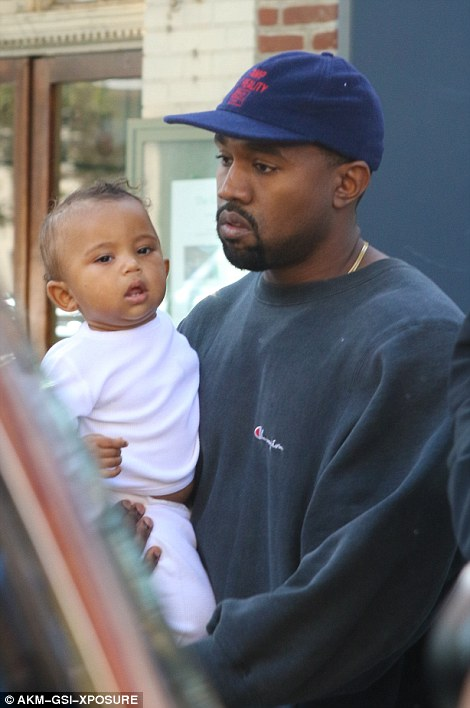Kanye West following his wife carrying little Saint West