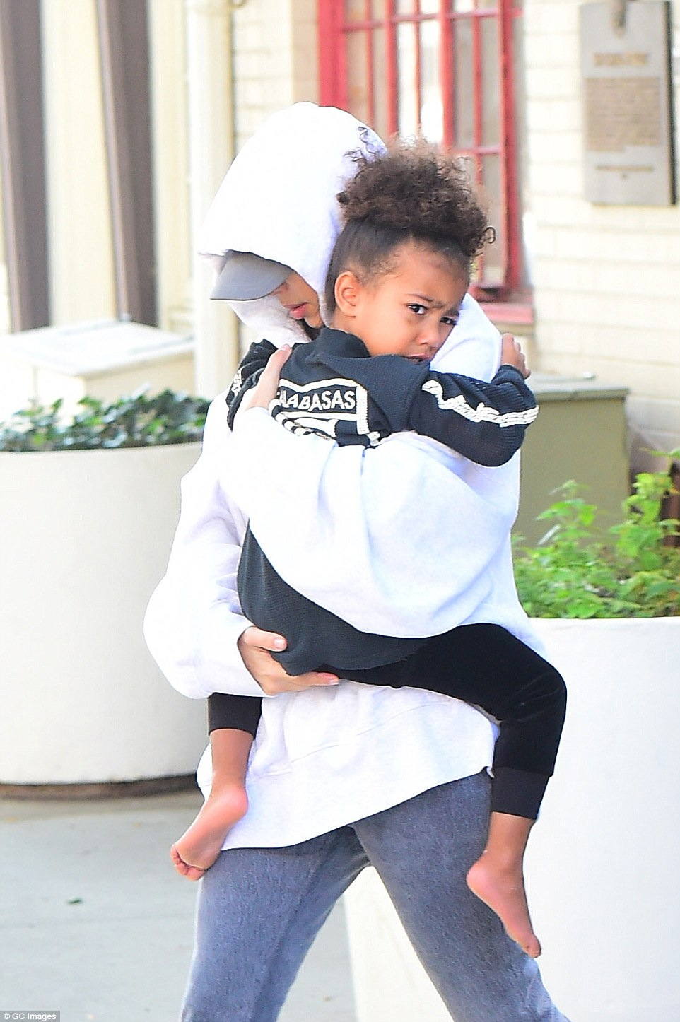 Security lapse: Over the weekend, MailOnline was able to use the old code to access the building, walking unchallenged all the way through to the reception area. Pictured: Devastated Kim clings to her daughter North in LA after returning following the robbery