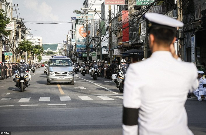 Police officers lined the streets to keep the crowds back as the king's body was driven through the streets of Bangkok on Friday