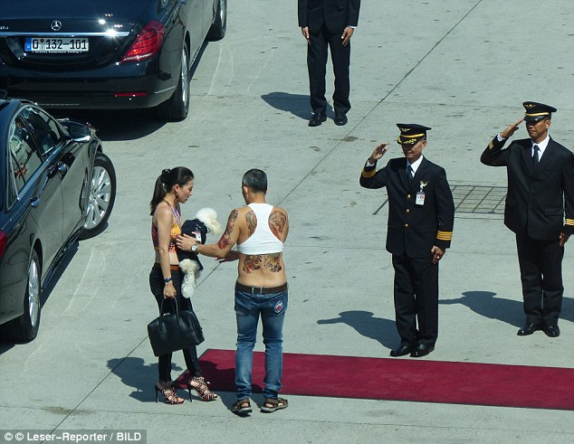 Crown Prince Maha Vajiralongkorn, a rumoured notorious womaniser, will be Thailand's new king after the death of his father, King Bhumibol on Thursday. Pictured: Prince Maha in Germany in May wearing a tank top, and covered in fake tattoos being received by officials