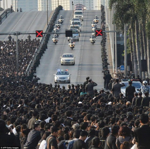 A van carries the body of King Bhumibol Adulyadej's to his palace as thousands of people line the street dressed in black