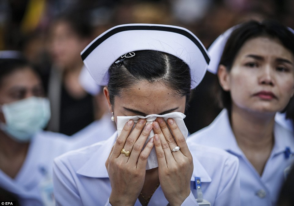 A well-wisher dries her tears with a handkerchief as a convoy of vehicles carrying the King's body arrives at the Grand Palace