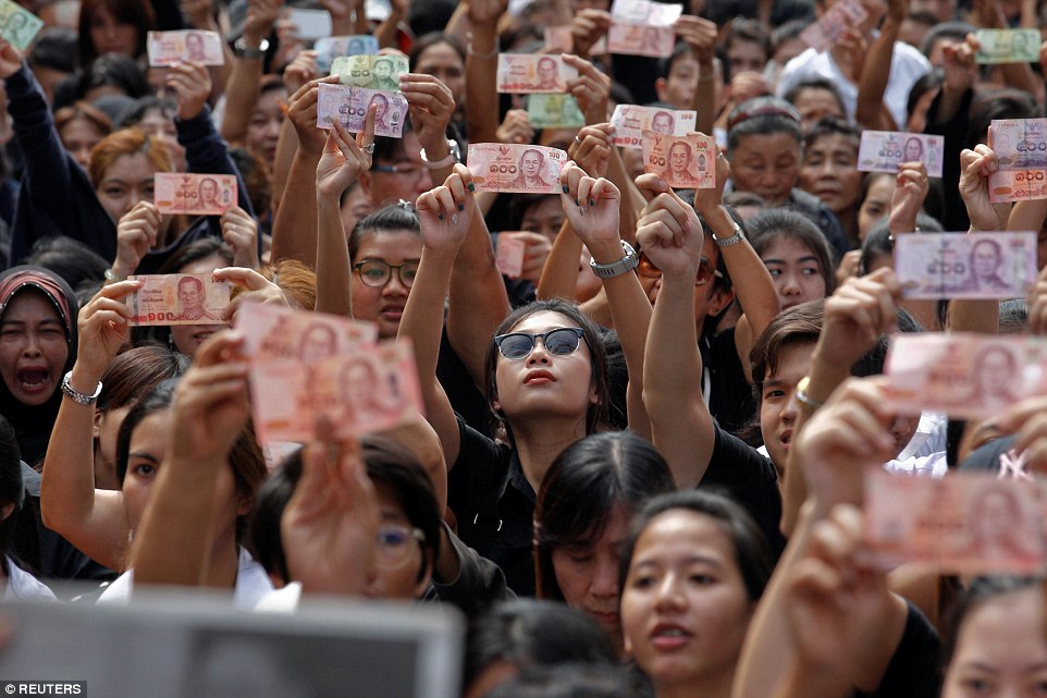 Hundreds of mourners held up Thai baht notes featuring King Bhumibol Adulyadej's image in the capital Bangkok