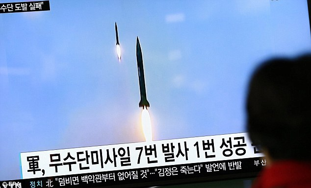 South Koreans watch a television news broadcast at a station in Seoul - according to media reports, North Korea had a failed ballistic missile launch the day before