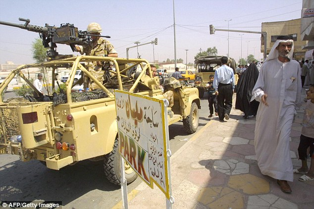 A British army patrol drives through the streets near Basra in 2003. Six British Red Caps were shot dead the day before