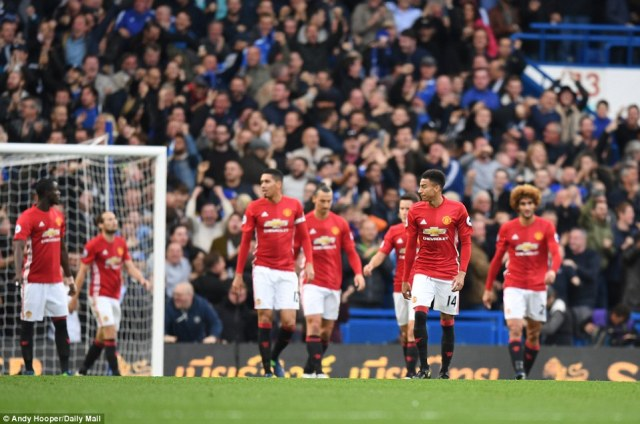 Manchester United players show their dejection after conceding another goal on a rough afternoon at Stamford Bridge