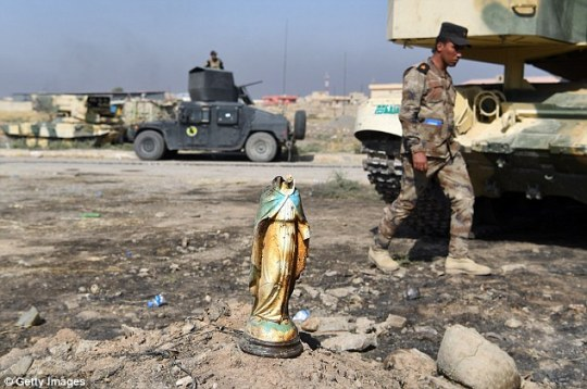 An Iraqi soldier walks past of broken statue of the Virgin Mary after liberating the town of Bartella