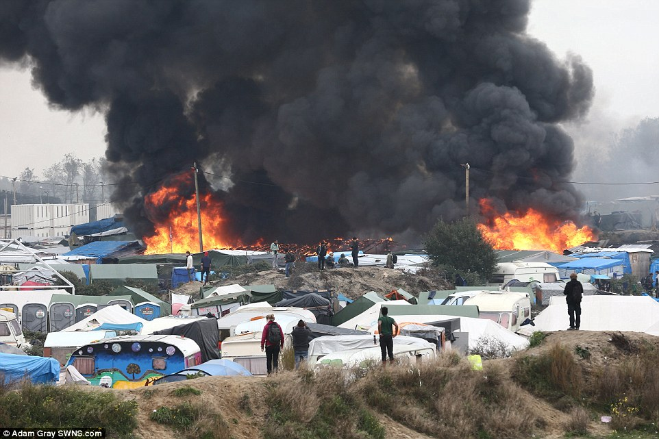 Calais burning: Migrants watch on as a huge fire rips through tents and huts in the heart of the Calais Jungle this morning