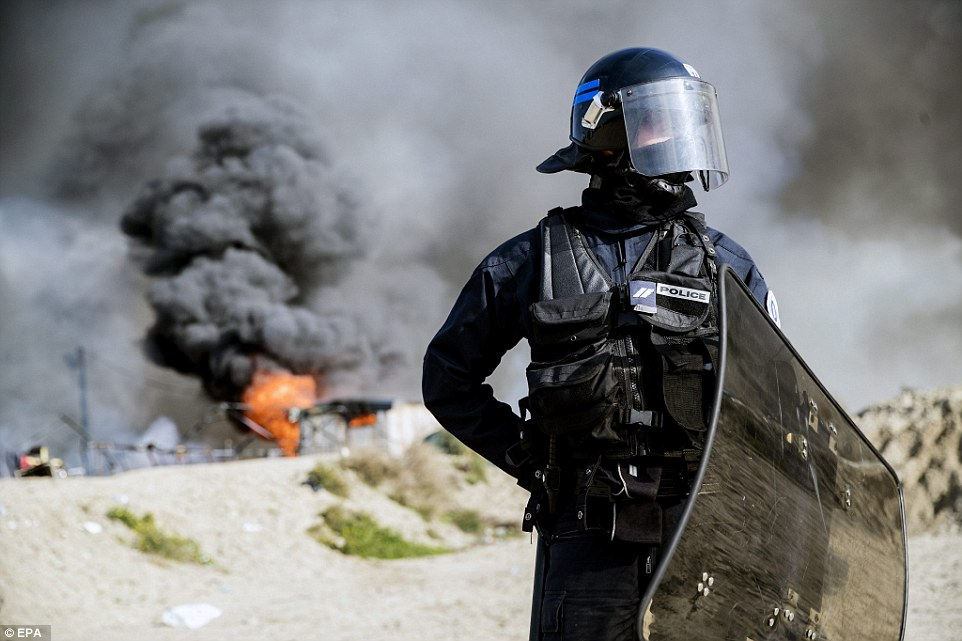 A French riot police officer forbids migrants  to access the makeshift camp 'The Jungle' after several fires set the whole area on fire during its evacuation in Calais on Wednesday
