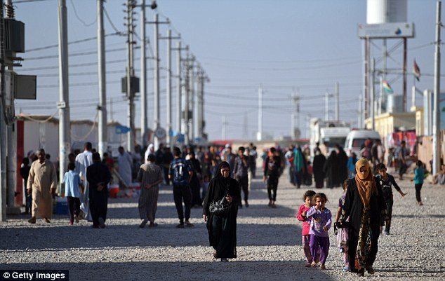 Families walk through the Debaga refugee camp where people displaced by fighting in and around Mosul have sought shelter