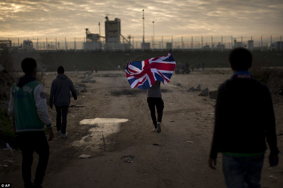 Moving out: A migrant runs with a British flag above his head inside the Jungle camp near Calais. As part of the camp's clearance, 3,242 adults have been transferred to centres around France since Monday and 772 unaccompanied minors have been moved to shipping containers converted into temporary shelters in the Jungle, the interior ministry said