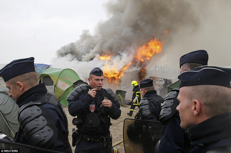 French Police have been told anarchists from the protest group 'No Borders' were responsible for starting the fire, which created a huge cloud of black smoke above the sprawling shantytown