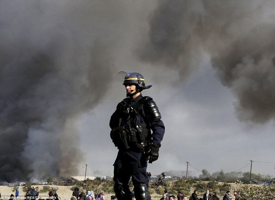 A young woman was gang raped during the destruction of the Calais Jungle, French prosecutors revealed today. A riot police officer is pictured during the clearance yesterday
