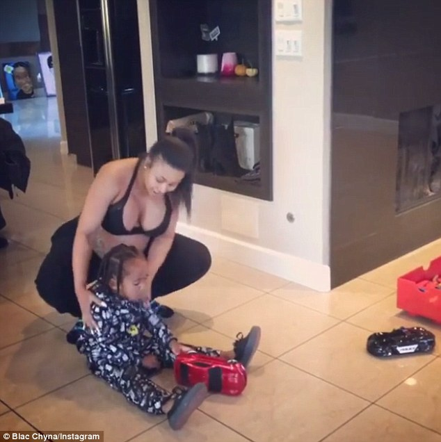Her pride and joy: After dancing into the living room, Chyna crouches down and wraps her arms around son King Cairo in a bid to get him to join in