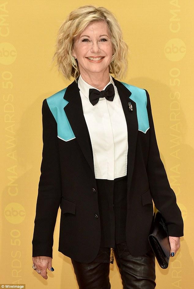 loucura Menswear!  O olhar de Olivia Newton-John foi um grande perder quando ela vestiu sua visão sobre um smoking completo com gravata borboleta