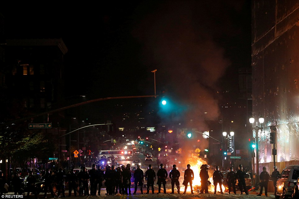 Oakland: Police form a barrier after demonstrators set a street on fire