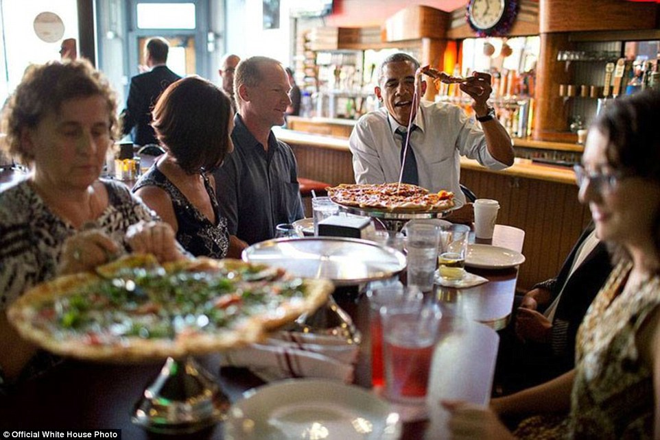 President Barack Obama shares a pizza dinner with individuals who wrote letters to him, at the Wazee Supper Club in Denver, Coloorado, July 8, 2014