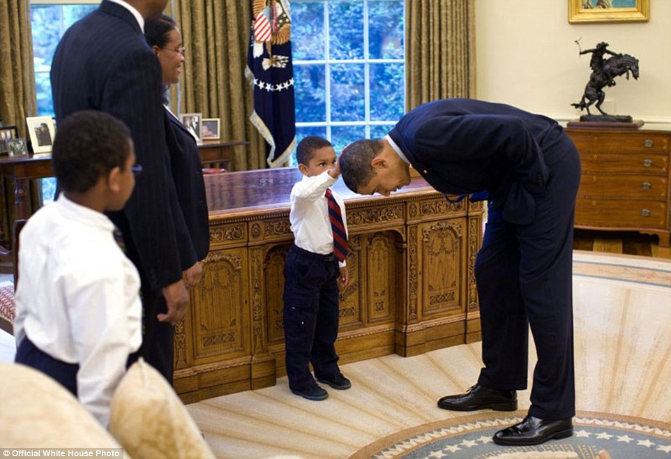 May 8, 2009. Obama bends over so the son of a White House staff member can pat his head during a visit to the Oval Office