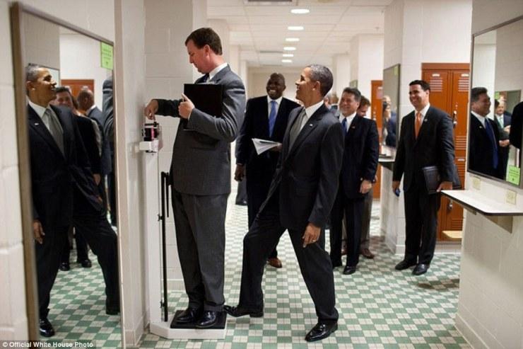 9 août 2010. Obama met son orteil à l'échelle en tant que directeur de voyage Marvin Nicholson essaie de se peser pendant une attente dans le vestiaire de volley-ball à l'Université du Texas à Austin