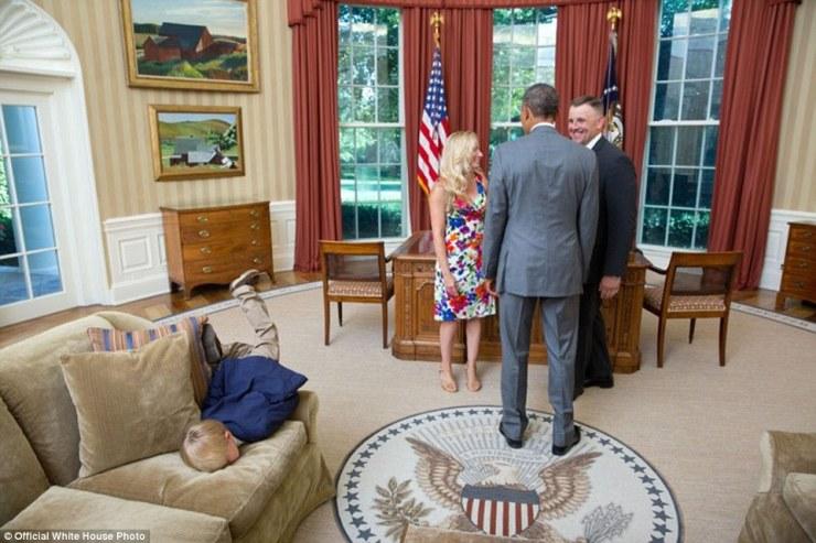 Le président Barack Obama visite avec un agent United States Secret Service au départ et sa femme comme leur fils plonge dans un canapé dans le bureau ovale, le 23 Juin, 2014