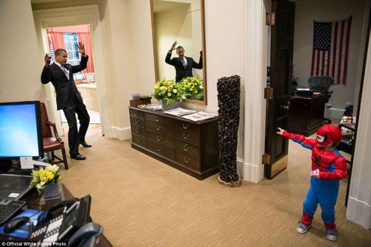 26 octobre 2012. Obama prétend être pris dans la toile de Spider-Man comme il salue Nicholas Tamarin, 3, juste à l'extérieur du bureau ovale. Spider-Man avait été trick-or-traitant pour un début de Halloween avec son père, la Maison Blanche aide Nate Tamarin