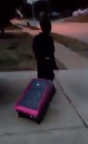 In the video, the child is seen pulling the suitcase as he walks past their driveway after she kicked him out