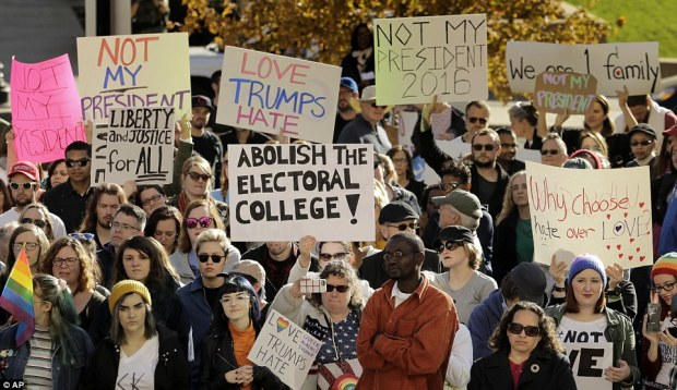 A large crowd of demonstrators hold anti-Donald Trump signs during a Missouri rally against the President-elect