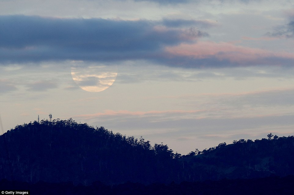 Clouds momentarily block the full view of the incredible supermoon that sparkled against the waters of Hobart on Monday