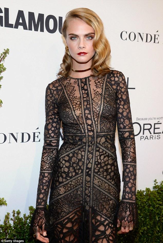 Figura Modelo: usando uma gargantilha de ouro, o modelo magro deslizou sua figura em uma Lacy vestido preto completo que deixou muito pouco à imaginação