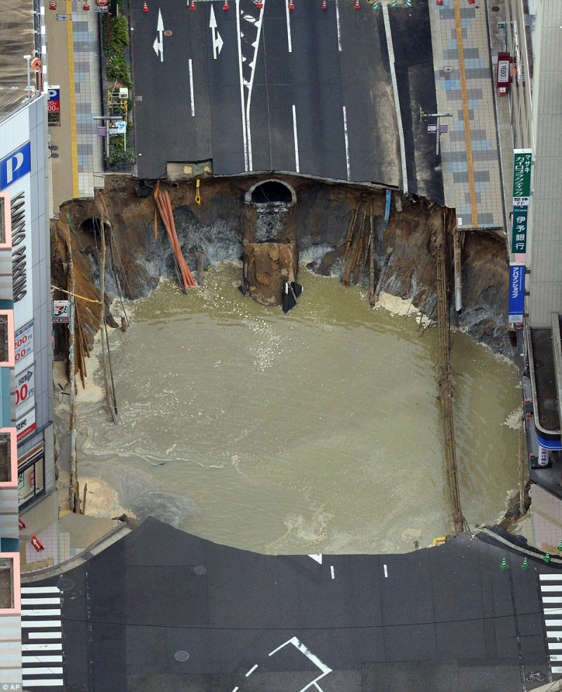 Burst water mains spewed a torrent of muddy water into the giant hole, which caused chaos in the city's business district