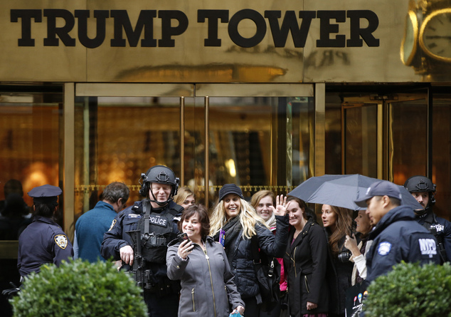 Trump Tower has quickly become one of the most popular selfie locations in New York City. Above, two women pose for a photo outside the gilded skyscraper with a heavily-armed NYPD officer on November 15