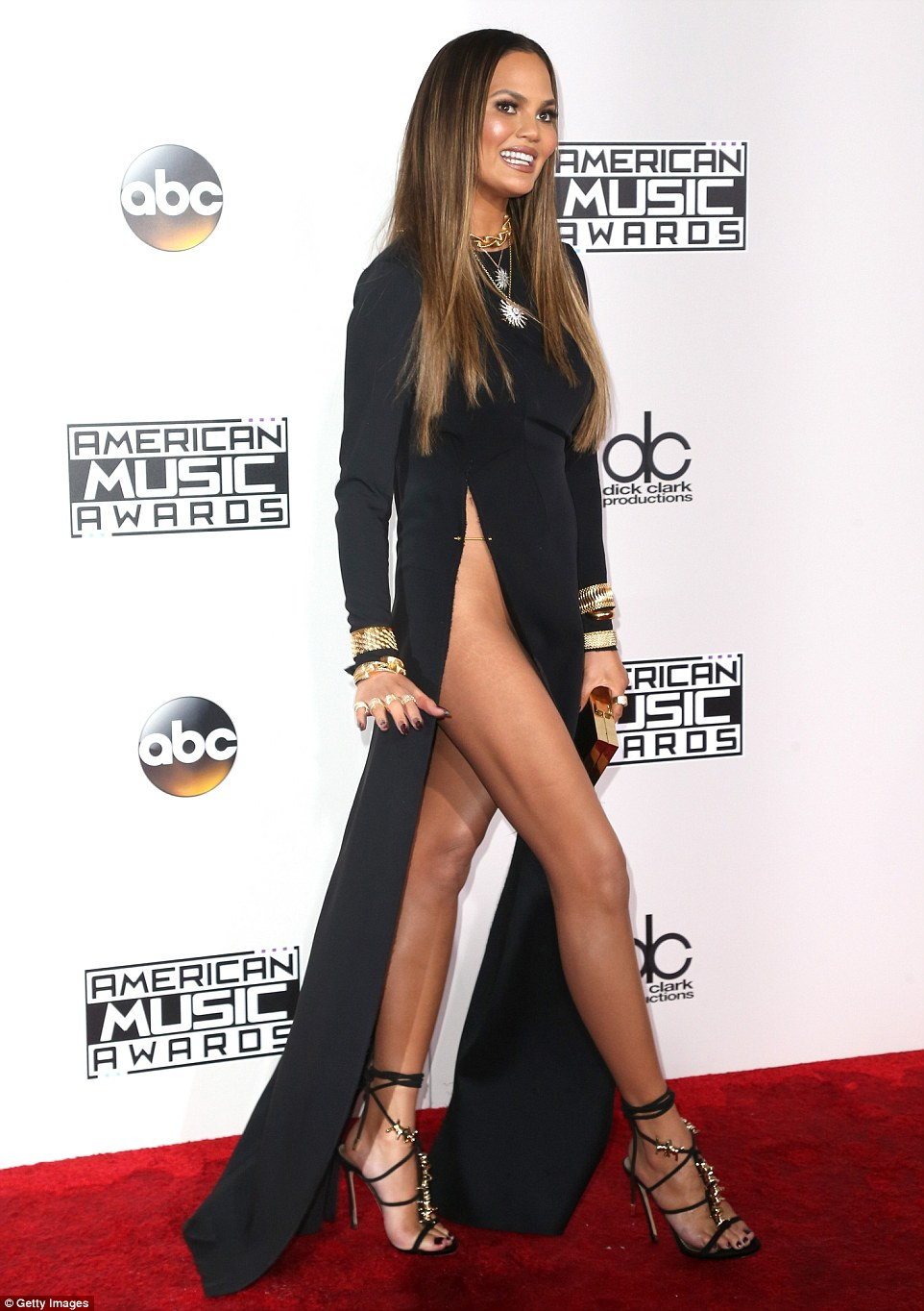 So revealing! Chrissy Teigen looked leggy in a black gown with impossibly high slit
