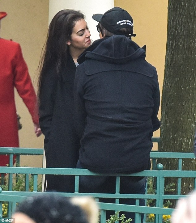 She's pleased: The brunette offered her boyfriend a coy smile during their tactile display