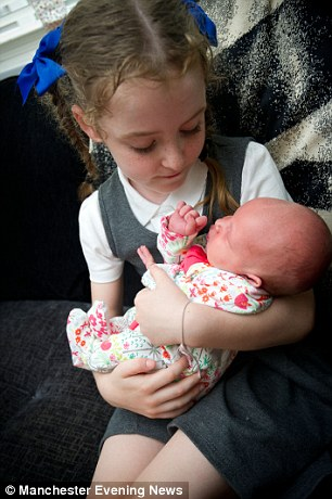 Sister Libby holds baby Elsie Rose, who was attached when she was just five-days-old