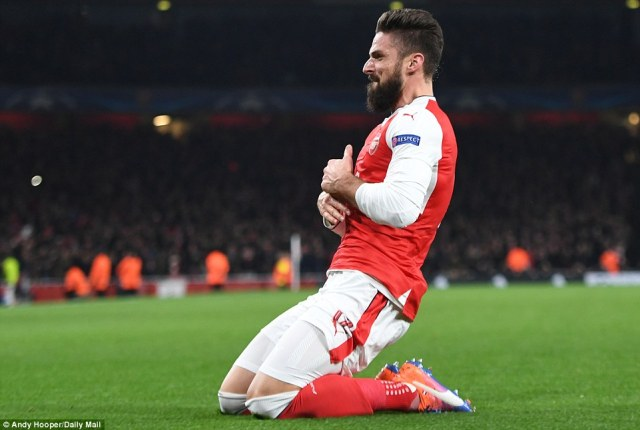 Olivier Giroud slides on his knees after scoring from the penalty spot to level the scores 1-1 for Arsenal at home against PSG